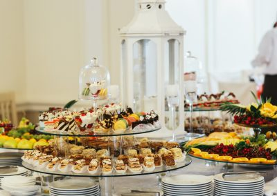 Large glass trays with sweets stand on the white buffet