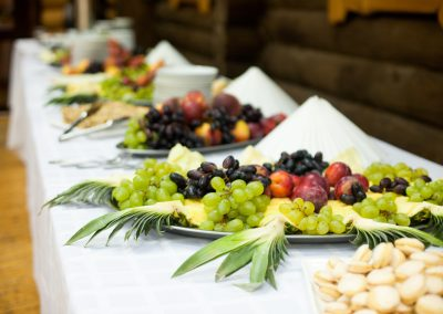 Large trays with fruits stand on the white buffet