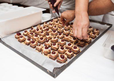 Chef in hotel or restaurant kitchen making dessert for dinner